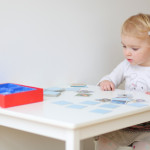 Adorable blonde toddler girl playing memory game